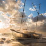 The ship ran aground during a storm. Sunset, water spray, high waves.